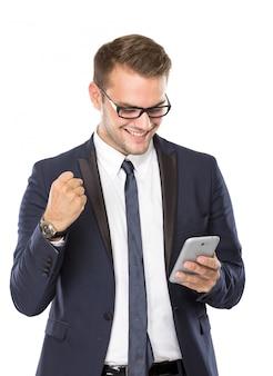 Giovane uomo d'affari che ha buone notizie mentre esaminando il suo handphone