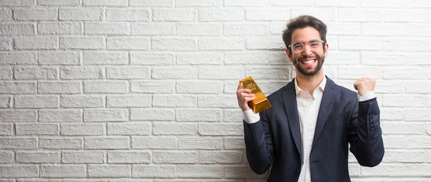 Giovane uomo d'affari che indossa un abito contro un muro di mattoni bianchi molto felice ed emozionato