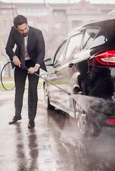 Giovane uomo d'affari che lava la sua automobile nell'autolavaggio.