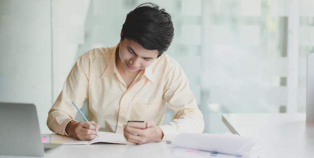 Giovane uomo d'affari che lavora al suo progetto mentre scrivendo sul taccuino