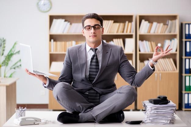 Giovane uomo d'affari che medita in ufficio