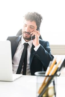 Giovane uomo d'affari che parla sul telefono cellulare sul posto di lavoro