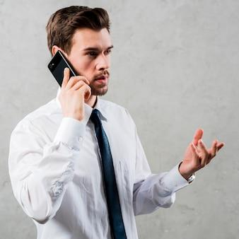 Giovane uomo d'affari che parla sullo smart phone che gesturing stando contro la parete grigia