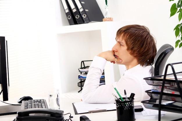 Giovane uomo d'affari che pensa nell'ufficio
