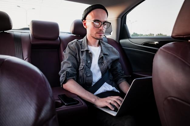 Giovane uomo d'affari che per mezzo del computer portatile su un sedile posteriore di un'automobile.