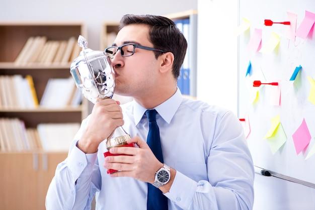 Giovane uomo d'affari che riceve la tazza premiata in ufficio