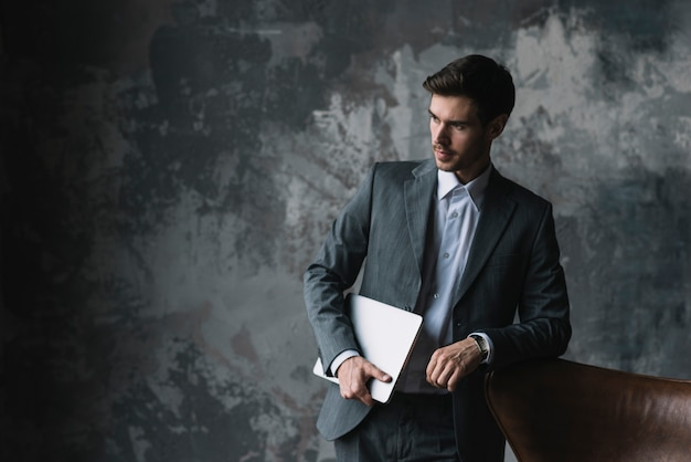 Giovane uomo d'affari che si appoggia sul computer portatile della holding della sedia in sua mano contro la priorità bassa del grunge