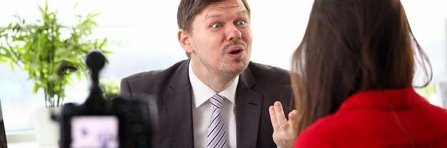 Giovane uomo d'affari che si sente pazzo e che esprime rabbia al collega della donna