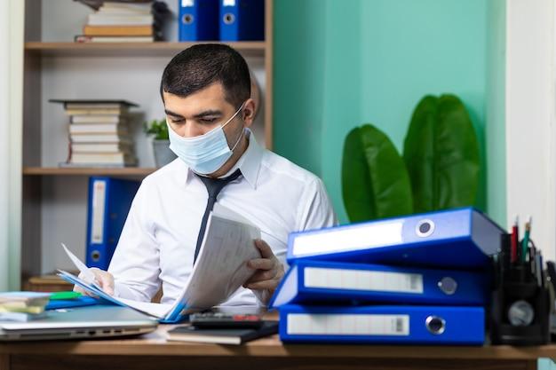 Giovane uomo d'affari che si siede alla tavola e che legge i documenti in ufficio con la mascherina e i guanti protettivi medici