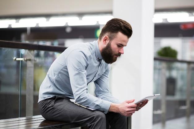 Giovane uomo d'affari che si siede sul banco facendo uso della compressa digitale