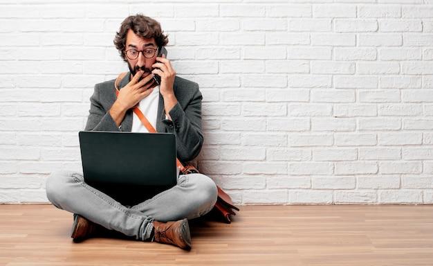 Giovane uomo d'affari che si siede sul pavimento con un computer portatile