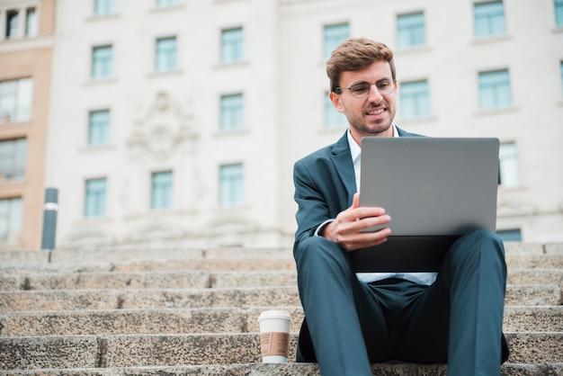 Giovane uomo d'affari che si siede sulla scala delle costruzioni facendo uso del computer portatile