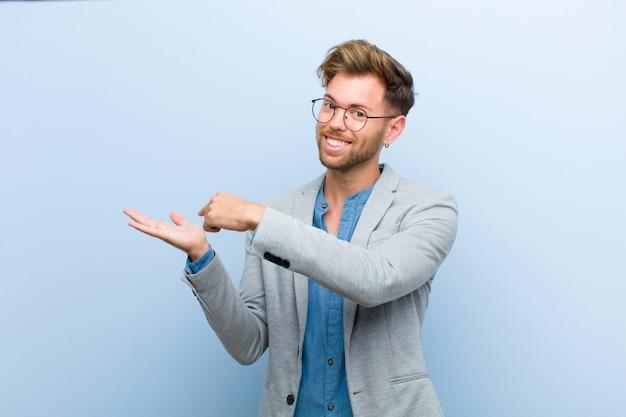 Giovane uomo d'affari che sorride allegramente e che indica lo spazio della copia sulla palma dal lato, mostrando o pubblicizzando un oggetto contro il blu