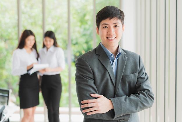 Giovane uomo d'affari che sorride con le braccia attraversate