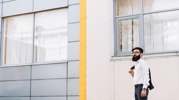 Giovane uomo d'affari che sta vicino all'edificio corporativo