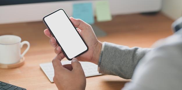 Giovane uomo d'affari che tiene smartphone schermo vuoto mentre si lavora sul suo progetto