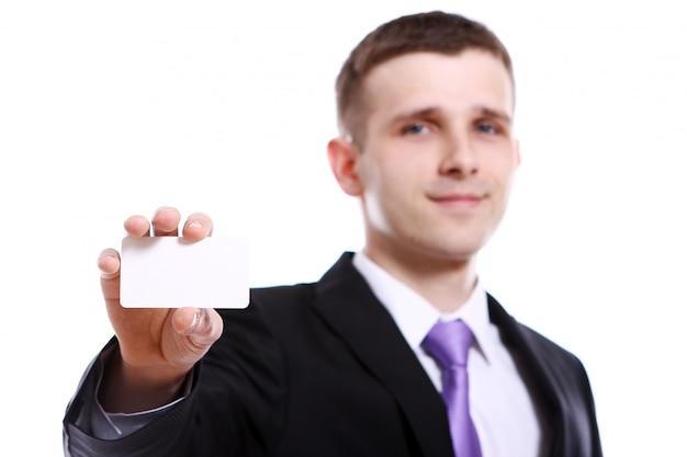Giovane uomo d'affari che tiene spazio in bianco vuoto