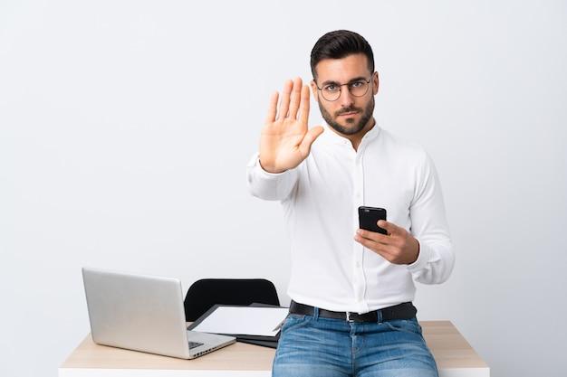 Giovane uomo d'affari che tiene un gesto di arresto di fabbricazione del telefono cellulare con la sua mano