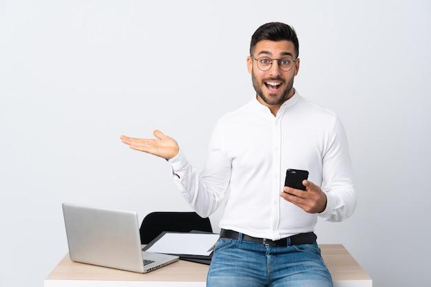 Giovane uomo d'affari che tiene un telefono cellulare che estende le mani al lato per l'invito a venire