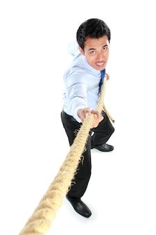 Giovane uomo d'affari che tira una corda mentre stando