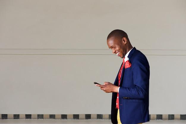 Giovane uomo d'affari che utilizza telefono cellulare e che cammina all'aperto