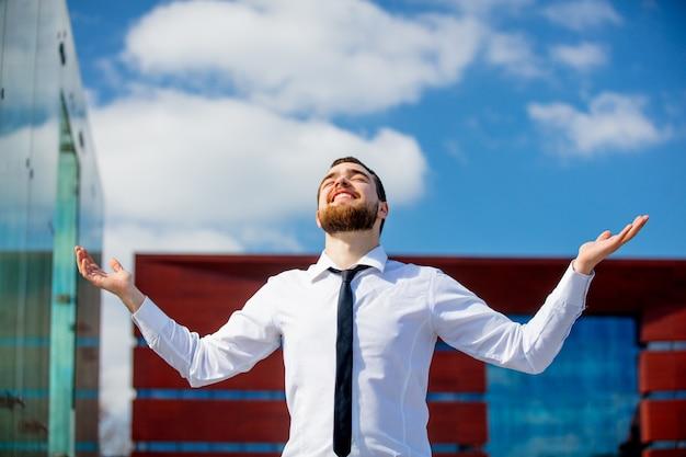 Giovane uomo d'affari con a braccia aperte in città all'aperto