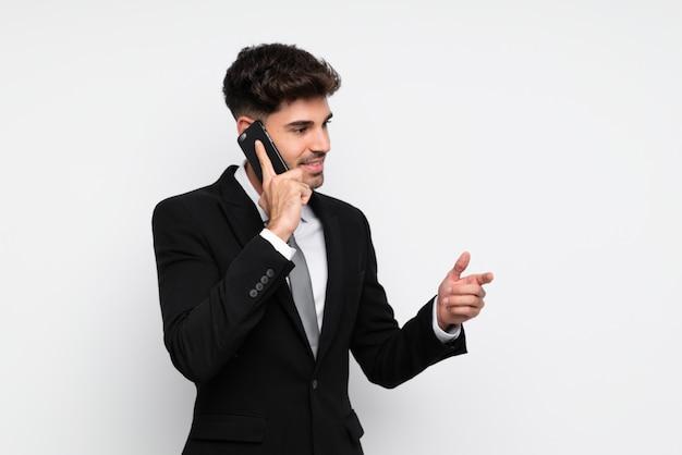 Giovane uomo d'affari con il telefono cellulare sopra bianco isolato