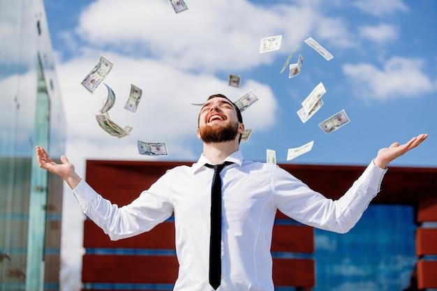 Giovane uomo d'affari con la caduta di denaro contante