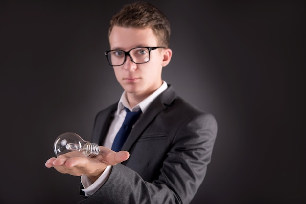 Giovane uomo d'affari con la lampadina nel concetto di idea