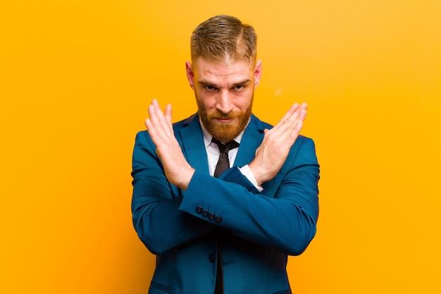 Giovane uomo d'affari con la testa rossa che sembra infastidito e stanco del tuo atteggiamento, dicendo abbastanza! le mani incrociate in avanti, ti dicono di fermarti contro l'arancia