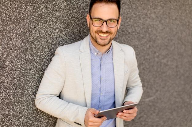 Giovane uomo d'affari con tavoletta digitale dalla parete grigia
