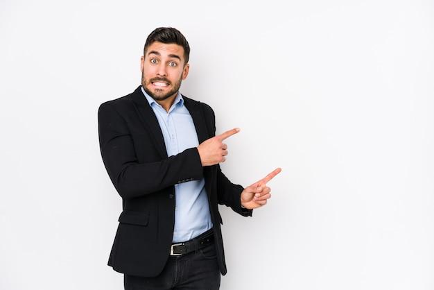 Giovane uomo d'affari contro un muro bianco isolato scioccato che puntava il dito indice verso uno spazio di copia