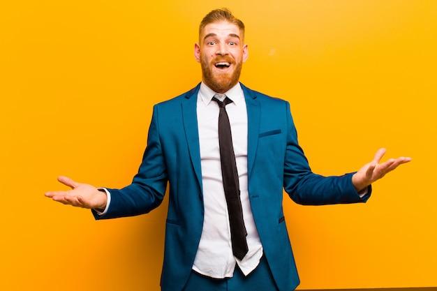 Giovane uomo d'affari dalla testa rossa a bocca aperta e stupito, scioccato e stupito con un'incredibile sorpresa contro l'arancia