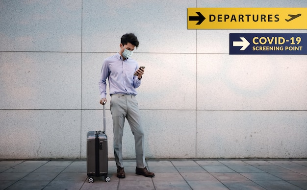 Giovane uomo d'affari del passeggero che indossa maschera chirurgica. utilizzando smartphone. in piedi con i bagagli in aeroporto.