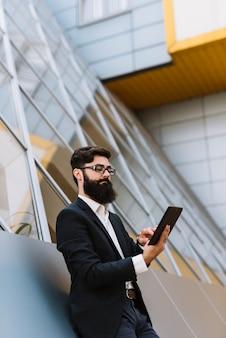 Giovane uomo d'affari della barba che si appoggia parete guardando smartphone