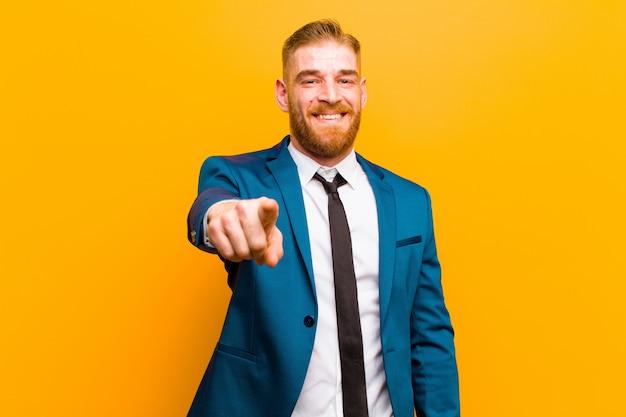 Giovane uomo d'affari della testa rossa che indica alla macchina fotografica con un sorriso soddisfatto, sicuro, amichevole, scegliente contro il fondo arancio