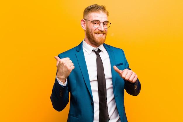 Giovane uomo d'affari della testa rossa che sorride allegramente e con indifferenza indicando il copyspace dal lato, sentendosi felice e soddisfatto contro l'arancia