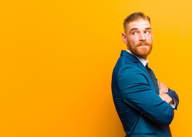 Giovane uomo d'affari della testa rossa che sorride allegramente, sentendosi felice, soddisfatto e rilassato, con le braccia incrociate e guardando al lato contro l'arancia