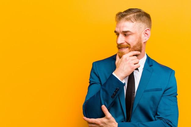 Giovane uomo d'affari della testa rossa che sorride con un'espressione felice e sicura con la mano sul mento, domandandosi e guardando al lato contro l'arancia