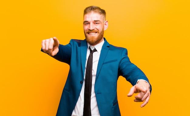 Giovane uomo d'affari della testa rossa sentirsi felice e fiducioso, indicando la fotocamera con entrambe le mani e ridendo, scegliendovi contro l'arancia