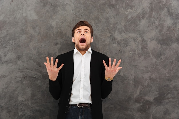 Giovane uomo d'affari di grido che controlla parete grigia