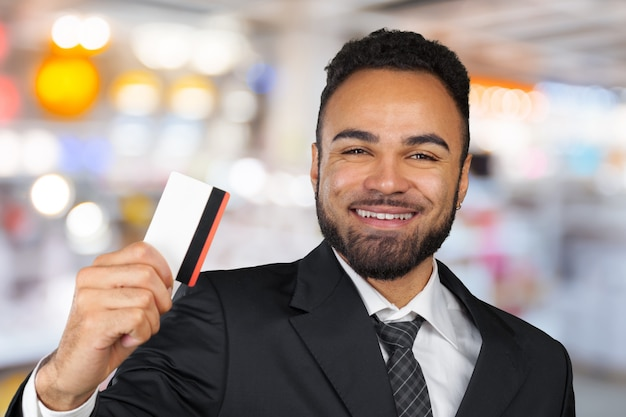 Giovane uomo d'affari di successo in un elegante abito classico nero in possesso di una carta di credito in plastica