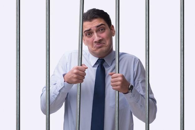 Giovane uomo d'affari dietro le sbarre in prigione