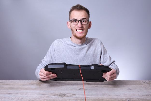Giovane uomo d'affari divertente del nerd che lavora al computer