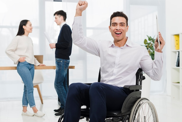Giovane uomo d'affari emozionante che giudica compressa digitale a disposizione che si siede sulla sedia a rotelle con le coppie di affari che se lo esaminano