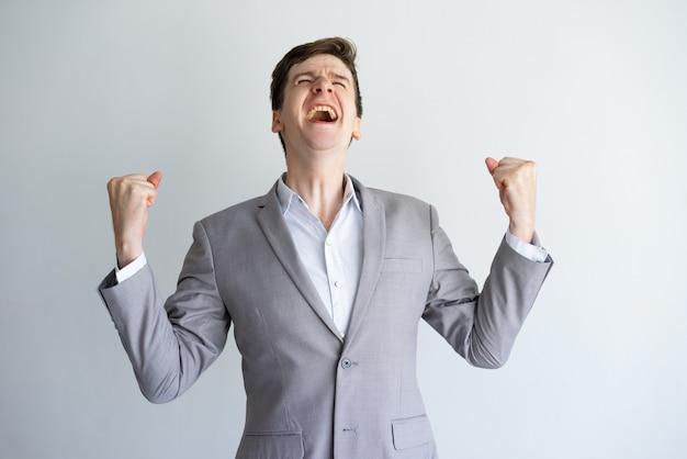Giovane uomo d'affari emozionante che gode del successo