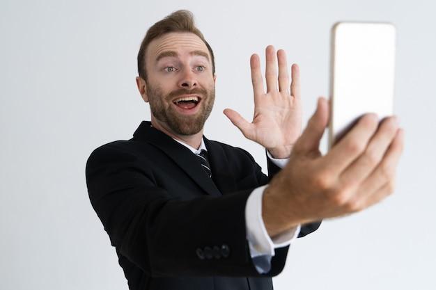 Giovane uomo d'affari emozionante che parla tramite collegamento video