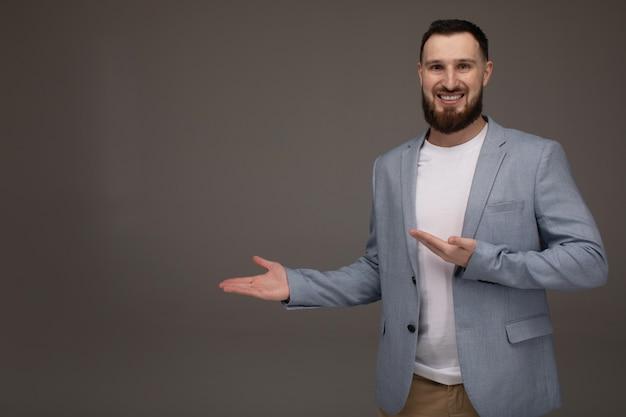 Giovane uomo d'affari felice che presenta isolato sopra la parete grigia. copyspace.