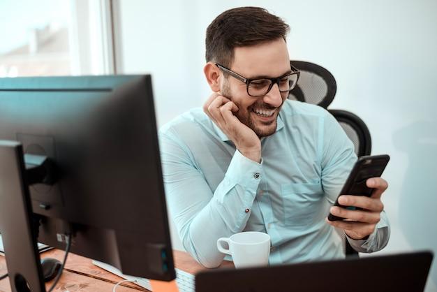 Giovane uomo d'affari felice che sorride mentre leggendo messaggio sul suo smartphone.