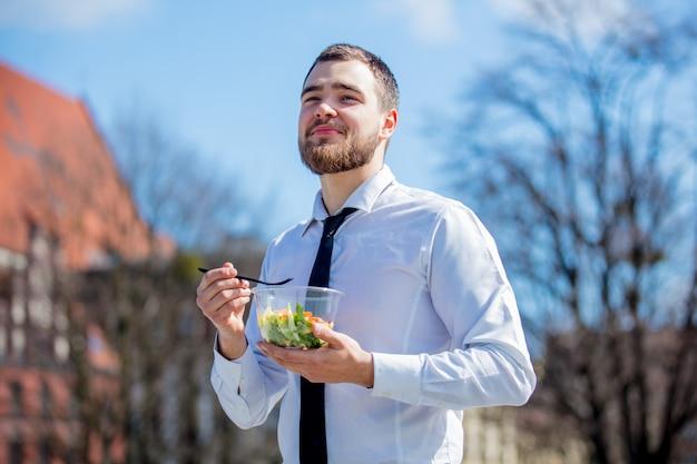 Giovane uomo d'affari in camicia e cravatta con scatola di pranzo insalata